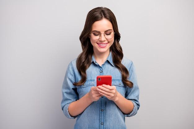 Фотография красивой креативной женщины-фрилансера, держащей просматривающий телефон, читать сообщение, писать новый блог, текст, носить спецификации, повседневные джинсы, джинсовая рубашка, изолированная серого цвета