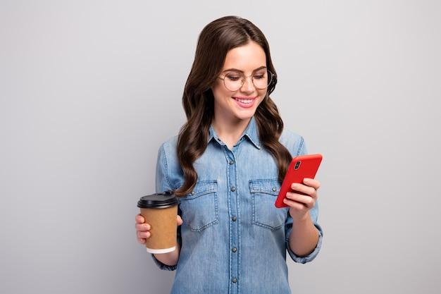 Фотография красивой женщины-фрилансера держит бумажный стаканчик горячий кофе, напиток, перерыв, просматривает телефон, прочтите, спецификации одежды, повседневные джинсы, джинсовая рубашка, изолированный серый цвет