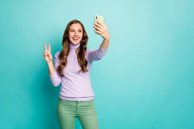 美しいおかしい女性の写真は、vサインのシンボルを示すセルフィーを作る緑のケースの電話を保持します紫のジャンパー緑のズボン分離ティールブルーパステルカラー