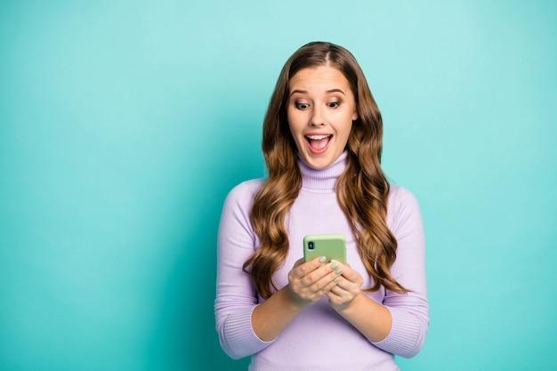 Фото красивой забавной дамы держите телефон за руки, читая сообщение в блоге, положительные комментарии, обрадованные носить фиолетово-фиолетовую водолазку, изолированную бирюзово-голубым пастельным цветом