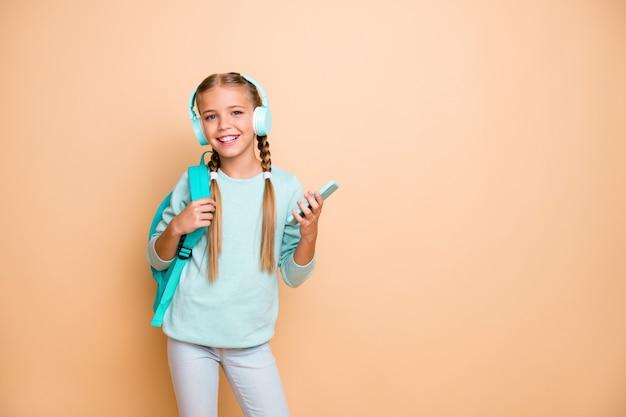 아름 다운 재미있는 작은 아가씨의 사진 들어 무선 이어폰 좋아하는 노래 산책 학교 검색 전화 착용 파란색 풀오버 청바지 절연 베이지 색 파스텔 컬러 벽