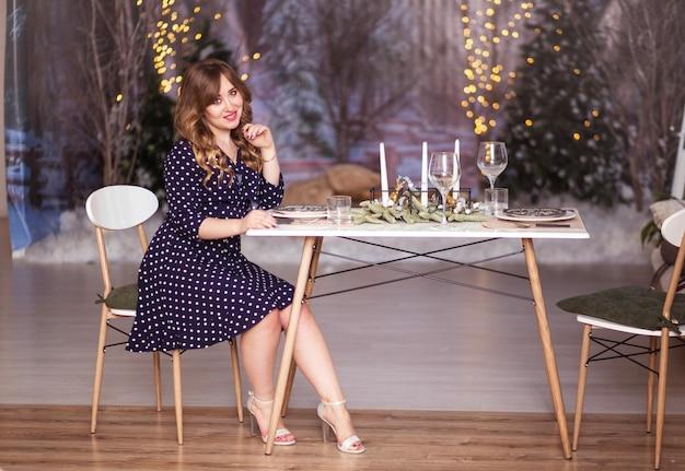 Фото красивая девушка в платье сидит за столом на рождество