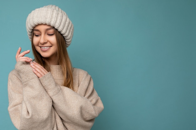 ベージュの暖かいセーターと下を見下ろしているニットベージュの帽子を身に着けている青い壁の壁の上に分離された美しい幸せなかわいい笑顔のセクシーな若いダークブロンドの女性の写真。コピースペース