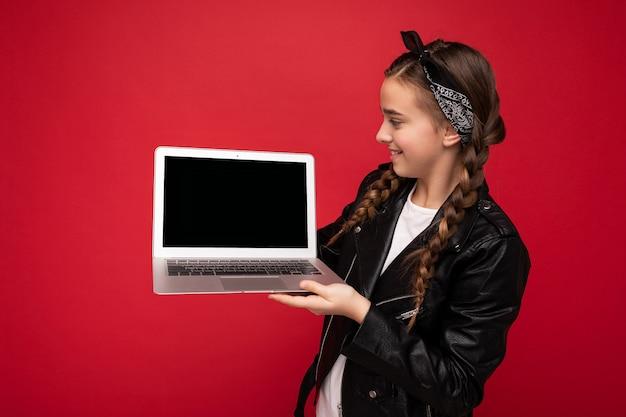 검은 자 켓과 노트북 모니터 디스플레이보고 빨간 벽 위에 절연 두건을 입고 netbook을 들고 brunet 땋은 아름 다운 행복 한 웃는 여자의 사진. 복사 공간,