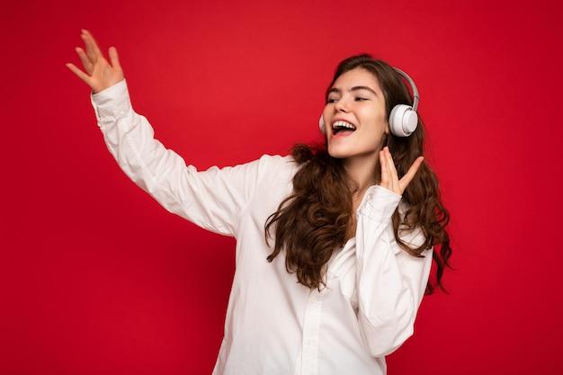 흰 셔츠와 안경을 쓴 아름다운 웃고 있는 젊은 브루네트 여성의 사진