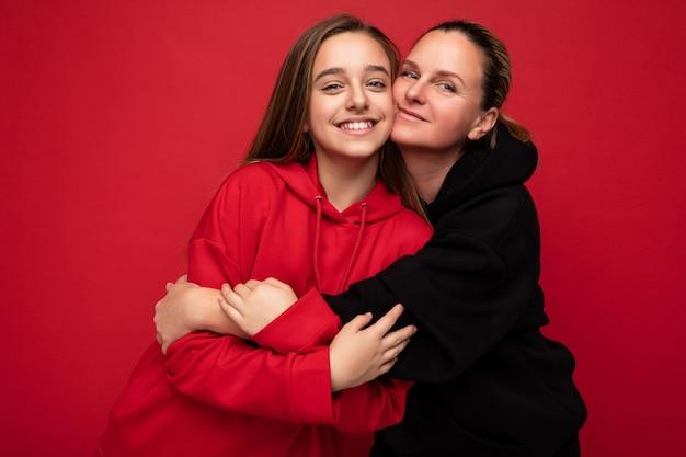 スタイリッシュな赤いパーカーを着て美しい幸せな笑顔の若い娘と流行の服を着て大人の母親の写真