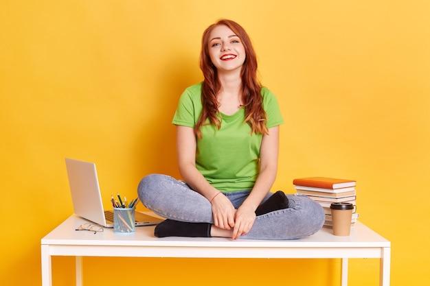 Фотография красивой счастливой женщины смотрит в камеру, сидя на белом столе