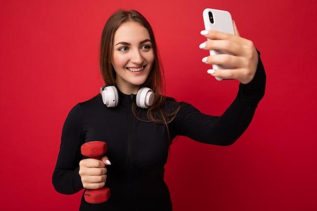 검은색 스포츠 옷을 입고 흰색 이어폰을 끼고 있는 아름다운 행복한 젊은 갈색 머리 여성의 사진