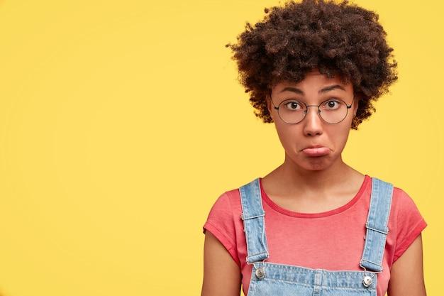カジュアルな服を着て、眼鏡をかけ、黄色い壁に向かってポーズをとる、美しい侮辱されたアフリカ系アメリカ人の女性の財布の唇の写真。困惑している気分を害した若い女性。顔の表情