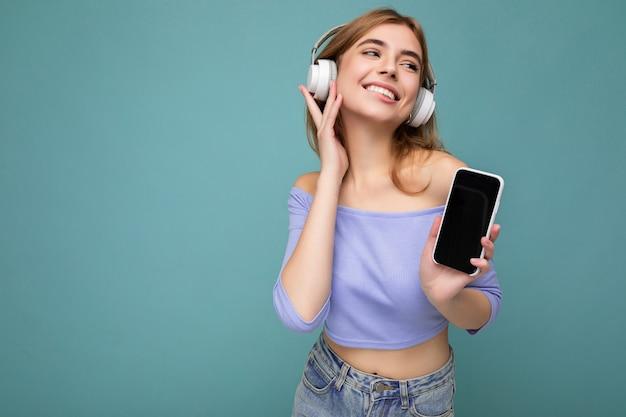 Фото красивой радостной улыбающейся молодой женщины в стильной повседневной одежде, изолированной над