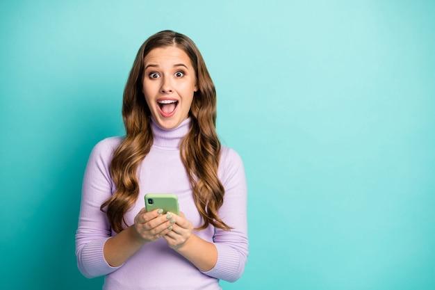 Фото красивой дамы держат телефон за руки читать сообщение в блоге положительные комментарии обрадованный открытый рот носить фиолетовый фиолетовый водолазку изолированный бирюзовый пастельный синий цвет