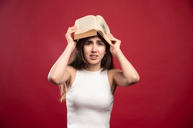 本を頭上に持っている美しい女性の写真