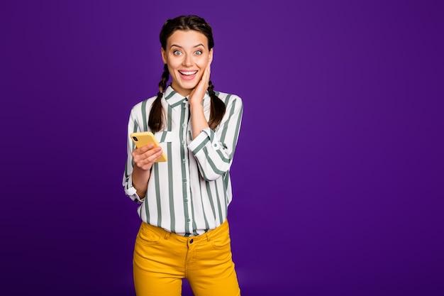 Фотография красивой дамы, держащей телефон, читает инстаграм пост положительных хороших комментариев и лайков в полосатой рубашке, желтые брюки, изолированный фиолетовый цвет фона