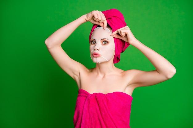 Фотография красивой женщины в душе нанесите коллагеновую хлопковую маску на лицо, носите полотенца, тело и голову изолировала зеленый цвет фона