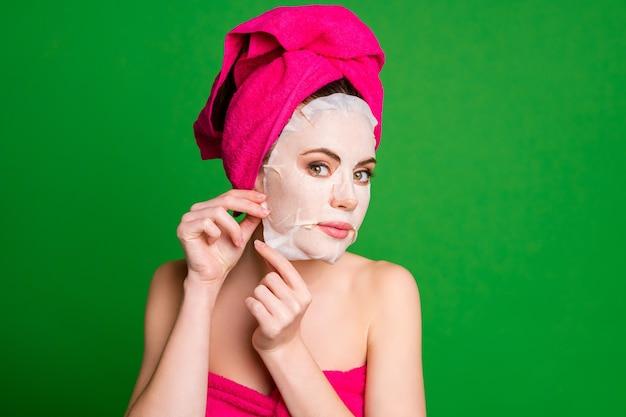 Фото красивой дамы снимают коллагеновую хлопковую маску для лица смотреть зеркало носить полотенца тело голова изолированные зеленый цвет фона