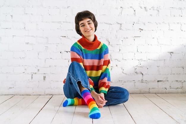 彼女の性的権利を誇りに思っている笑顔の表情を持つ美しいレズビアンの女性の写真は...