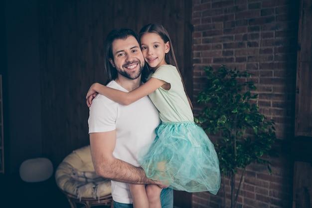 美しい小さな愛らしい女の子と夢のような笑顔を抱き締めるハンサムな若いパパの写真は、週末の時間を家庭的な家庭的な愛の雰囲気の家の部屋で過ごします