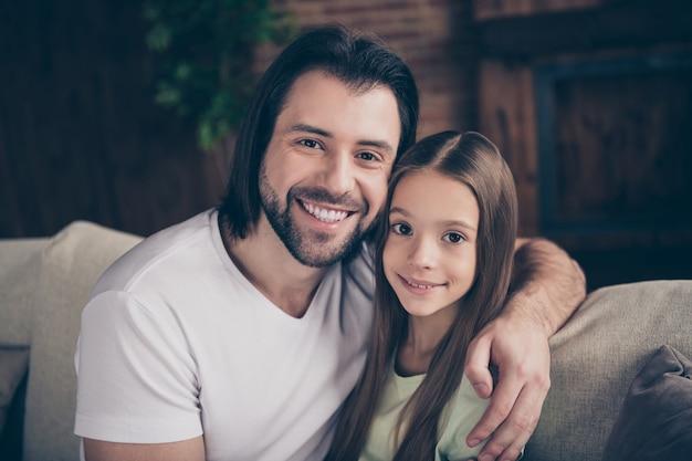 美しい小さな愛らしい女の子とハンサムな若いパパの写真は、夢のような笑顔を抱き締める快適なソファに座って週末の時間を家庭的な家庭の家の部屋で過ごします