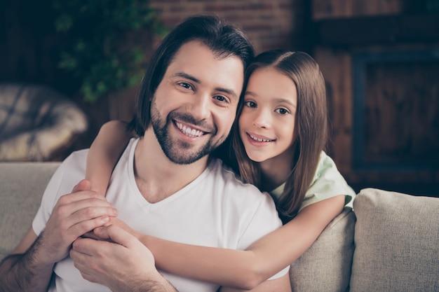 Фото красивой маленькой очаровательной девочки и красивого молодого папочки, сидящих на удобном диване