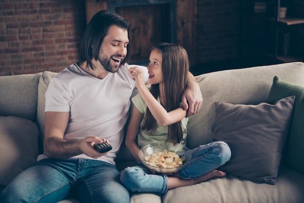 아름다운 작은 사랑스러운 소녀와 잘 생긴 젊은 아빠의 사진은 편안한 소파에 앉아
