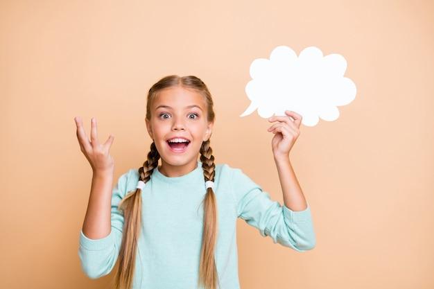 美しい小さな女性の写真は白い空の紙の雲を保持しますスマートな女子高生は正しい質問の答えを持っています青いプルオーバー分離ベージュパステルカラーの壁を着用してください
