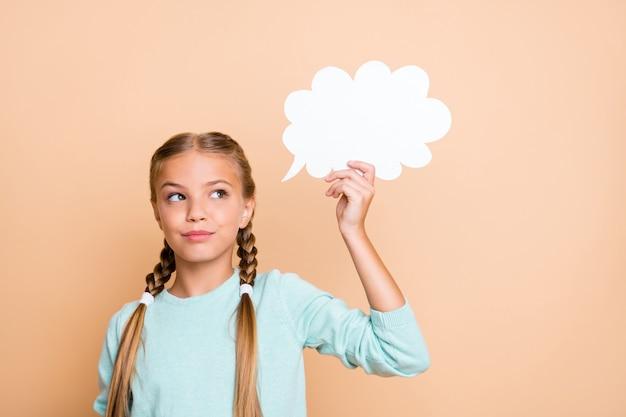 白い空の紙の雲を保持している美しい小さな女性の写真深い思考空のスペースを見てスマートな女子高生は青いプルオーバー分離ベージュパステルカラーの壁を着用