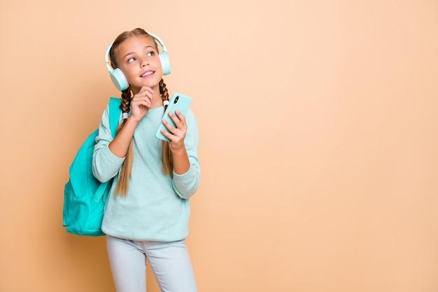 아름다운 아가씨의 사진 듣기 이어폰 좋아하는 노래 산책 학교 보류 전화 주말 착용 파란색 풀오버 청바지에 대한 꿈을 생각 베이지 색 벽 절연