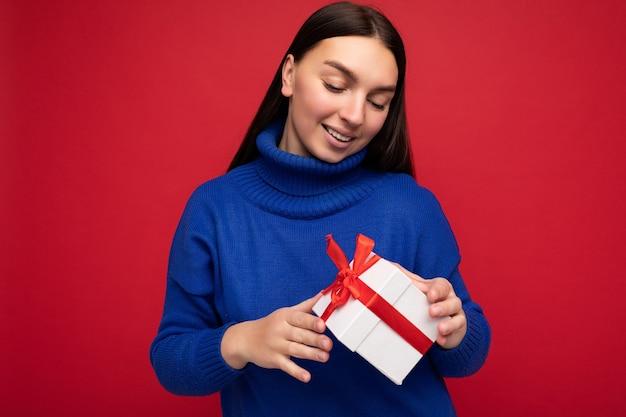 아름 다운 긍정적 인 웃는 젊은 갈색 머리 여자의 사진 입고 빨간 벽 위에 절연