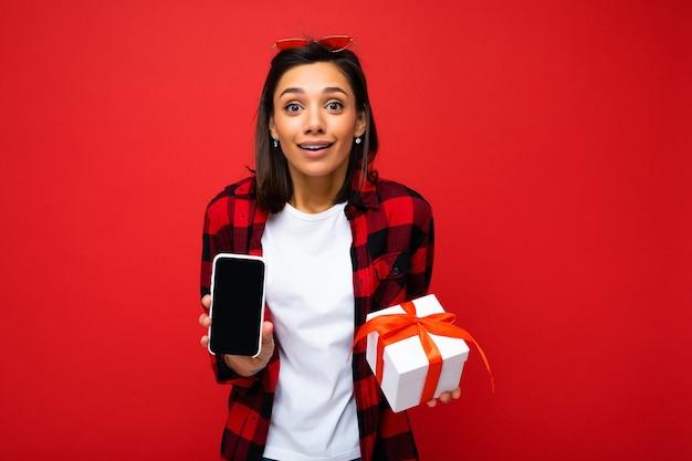 Фотография красивой позитивно удивленной молодой брюнетки, изолированной над красной фоновой стеной, в белой повседневной футболке и красно-черной рубашке, держащей белую подарочную коробку с красной лентой и мобильным телефоном