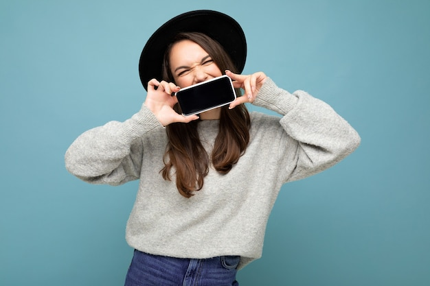 目を閉じて背景に分離されたスマートフォンを示す携帯電話を保持している黒い帽子と灰色のセーターを着ている美しいポジティブな女性の写真。モックアップ、切り抜き、空きスペース
