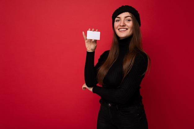 빨간색으로 격리된 검은색 스웨터와 모자를 쓴 아름다운 긍정적인 젊은 갈색 머리 여성의 사진