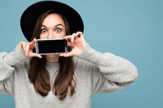 검은 모자와 회색 스웨터를 입고 카메라를 바라보는 배경에 격리된 스마트폰을 보여주는 휴대폰을 들고 있는 아름다운 긍정적인 젊은 여성의 사진.