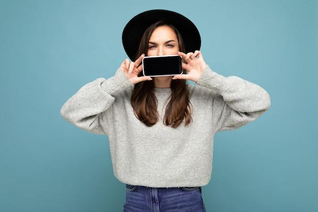 검은 모자와 회색 스웨터를 입은 아름다운 긍정적인 젊은 여성이 카메라를 바라보는 배경에 격리된 스마트폰을 보여주는 휴대폰을 들고 있는 사진.
