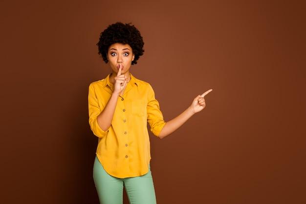 판매 쇼핑 가격을 조언하는 입술에 손가락 빈 공간 손가락을 나타내는 아름다운 꽤 어두운 피부 아가씨의 사진 노란색 셔츠 녹색 바지 절연 갈색 색상을 착용