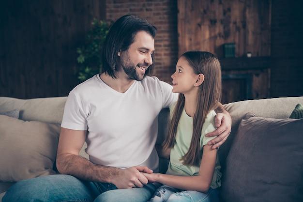 美しいかわいい女の子とハンサムなパパの写真は、週末の時間を家庭的な家庭的な家の部屋の屋内で過ごす笑顔の表情の目を抱き締める快適なソファに座っています