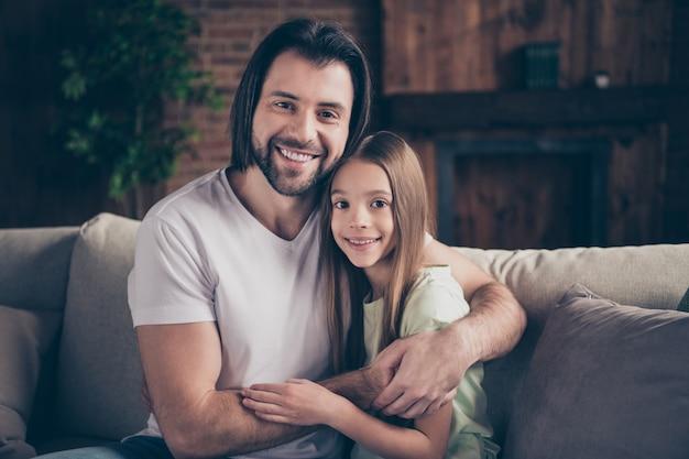 Фотография красивой симпатичной маленькой девочки и красивого папочки, сидящего на удобном диване, обнимающего вместе с очаровательной улыбкой, проводящего выходные в домашней домашней комнате в помещении