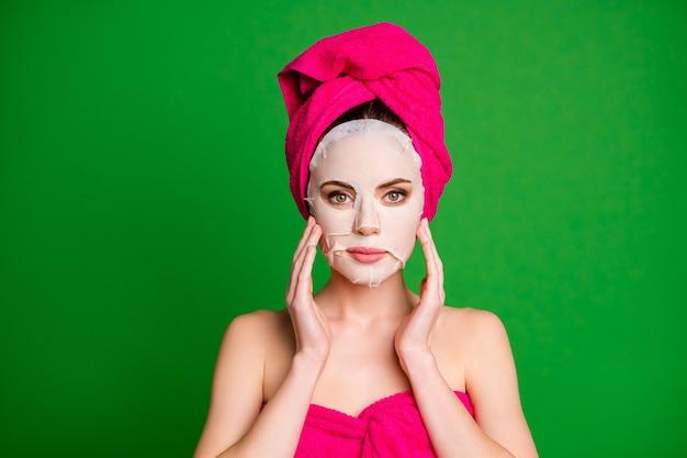Фото красивой расслабленной дамы применить коллагеновую маску для лица, руки, скулы, полотенца, тело, голова, изолированный зеленый цвет фона