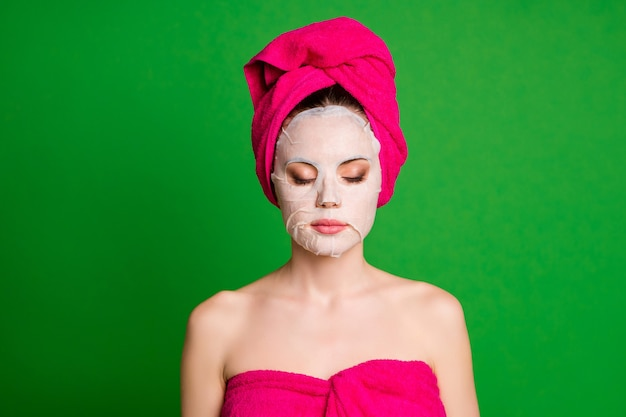 아름다운 편안한 여성의 사진은 콜라겐 마스크 눈을 감고 수건 바디 헤드 격리된 녹색 배경을 사용합니다.