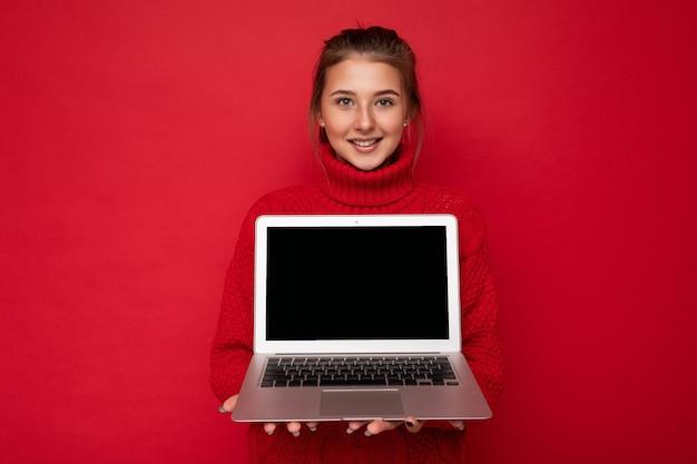 Фотография красивой довольной счастливой молодой женщины, держащей компьютерный ноутбук в красном свитере, изолированном над красной стеной. вырезать