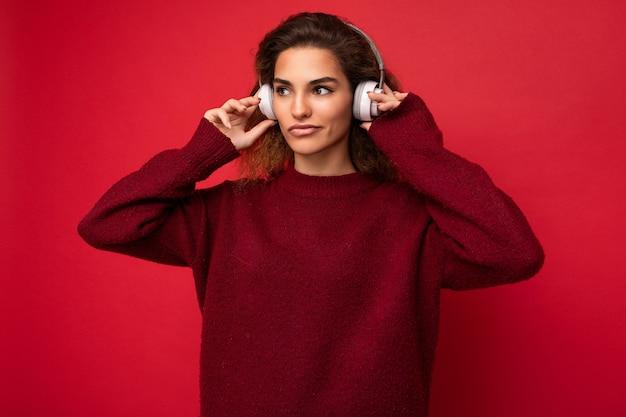 赤の上に分離された濃い赤のセーターを着ている美しい深刻な若いブルネットの巻き毛の女性の写真