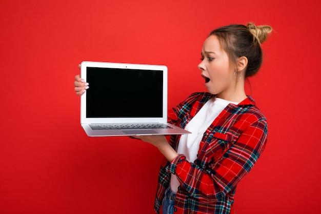 Фотография красивой потрясенной изумленной молодой женщины, держащей ноутбук в красной рубашке, смотрящей на дисплей монитора, изолированный на красном фоне. макет