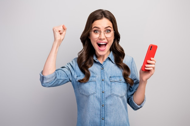 Фото красивой потрясенной волнистой дамы с телефоном проверяют подписчики подписчики читают новые положительные комментарии характеристики одежды повседневные джинсы джинсовая рубашка изолирована серого цвета