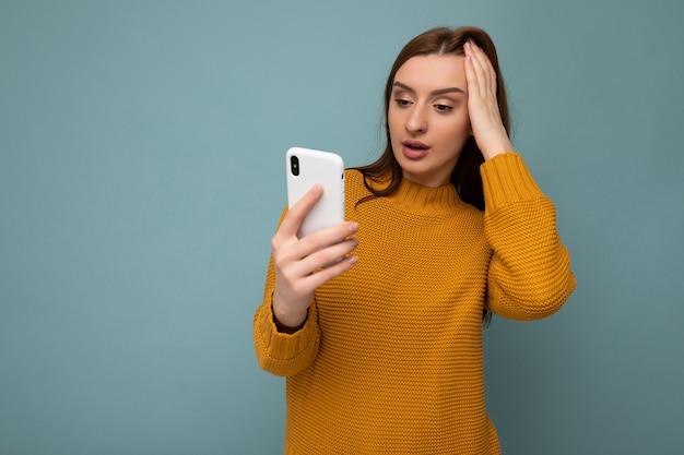 Фотография красивой потрясенной молодой женщины в оранжевом свитере, стоящей на синем фоне