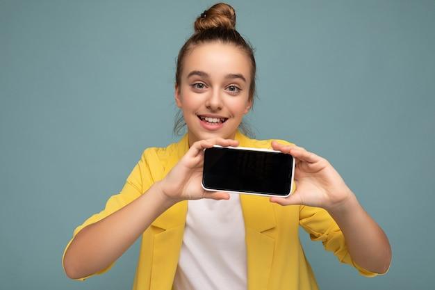 Фотография красивой улыбающейся девушки, хорошо выглядящей, одетой в повседневный стильный наряд, стоящая изолирована на фоне с копией пространства, держа смартфон, показывая телефон в руке с пустым экраном для макета