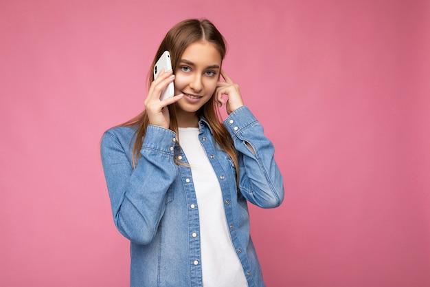 手に持ってカメラを見ながら携帯電話で話しているピンクの背景の上に分離されたカジュアルなブルージーンズのシャツを着て美しい笑顔の幸せな若いブロンドの女性のpesonの写真。