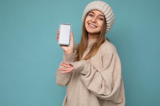 スタイリッシュなベージュのセーターとベージュを身に着けている美しい笑顔のポジティブな格好良い若い女性の写真