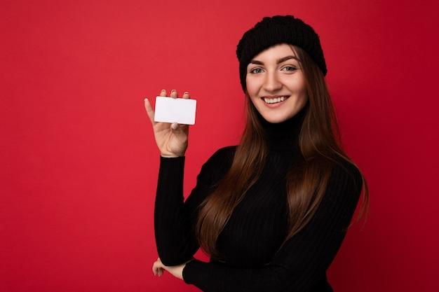 빨간색으로 격리된 검은색 스웨터와 모자를 쓴 아름다운 웃고 있는 젊은 갈색 머리 여성의 사진