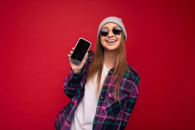 孤立した立っているカジュアルなスタイリッシュな服を着て格好良い美しい笑顔の若い女性の写真