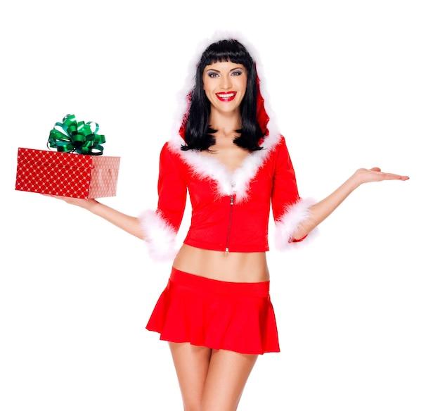 Фотография красивой снегурочки держит рождественскую подарочную коробку и что-то на пустых руках поднимает вверх - изолированные на белом