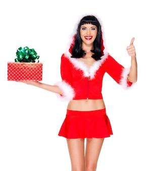 Фотография красивой снегурочки держит рождественскую новогоднюю подарочную коробку с большими пальцами руки вверх - изолированные на белом